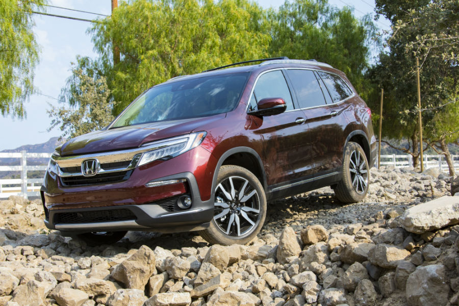 A photo of the 2019 Honda Pilot driving over a pile of rocks.