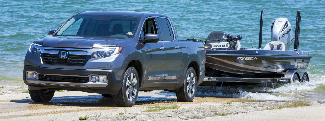 A photo of the Honda Ridgeline pulling a boat out of the water.
