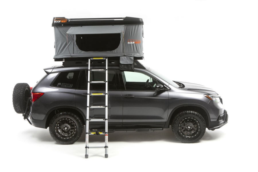 A right profile photo of the Honda Passport with a roof-mounted tent opened up.