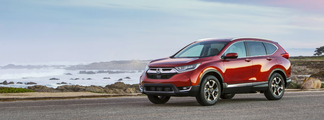 A left profile photo of the 2019 Honda CR-V parked in front of the ocean.