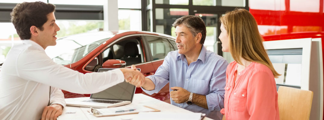 A stock photo of a couple signing sales paperwork.