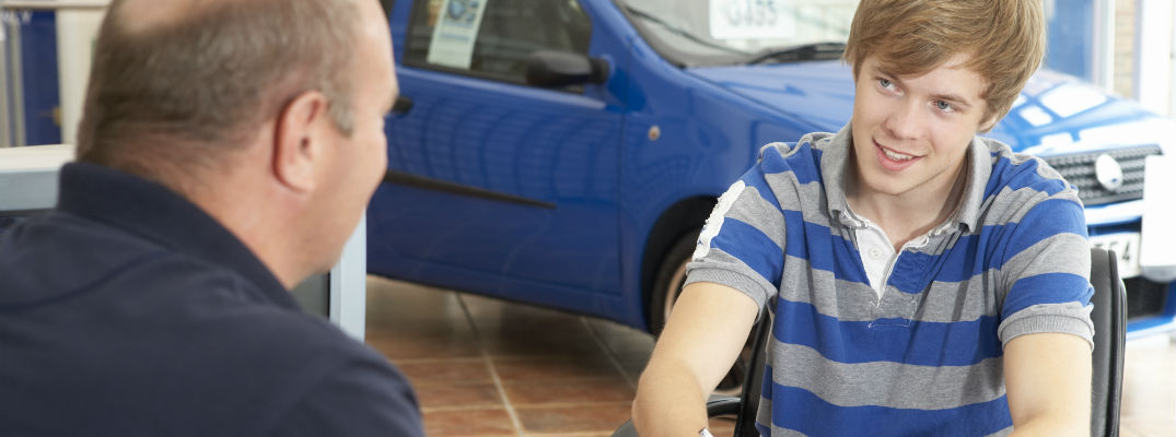 A stock photo of a young person signing some paperwork at a dealership.
