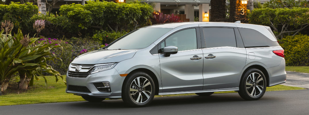 A left profile photo of the 2020 Honda Odyssey parked on the side of the road.
