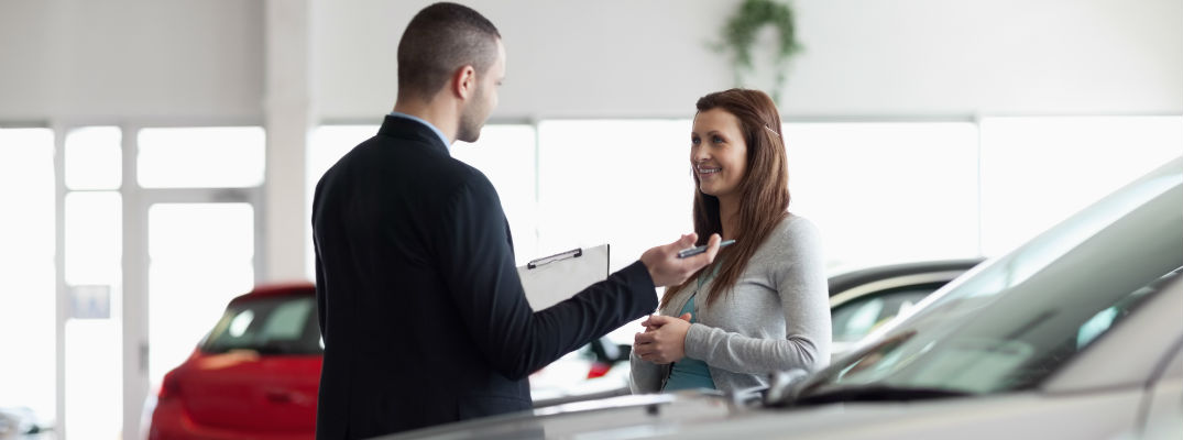 A stock photo of a person working with a dealership representative.