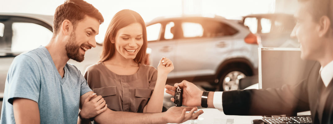A stock photo of a young couple getting a new set of keys for the new vehicle.