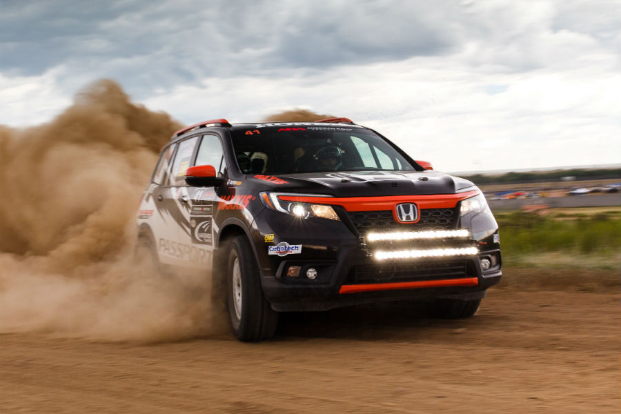 A photo of a specialized Honda Passport driving through the desert.