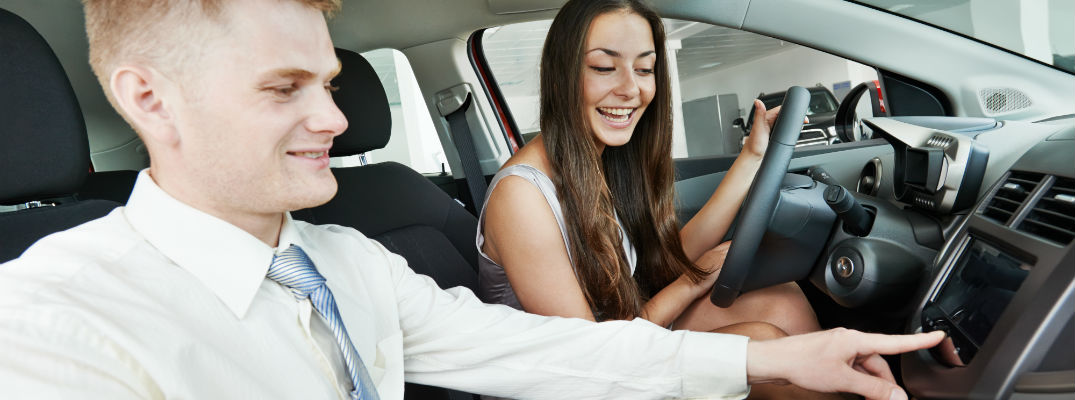 A stock photo of a person learning about the features of a new car.