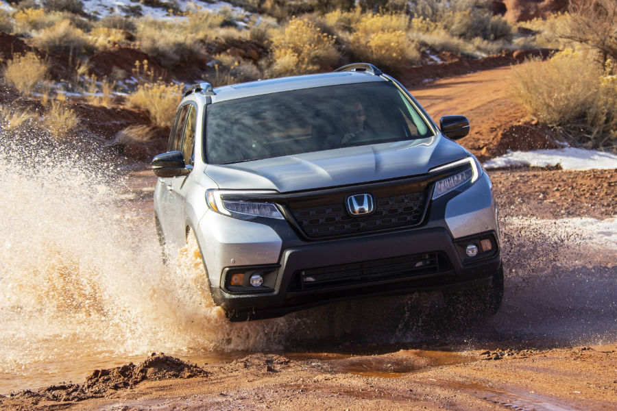 A photo of the 2020 Honda Passport driving through a large puddle.