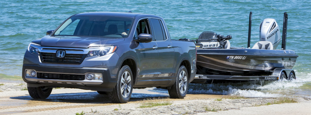 A photo of a 2020 Honda Ridgeline pulling a boat out of the water.