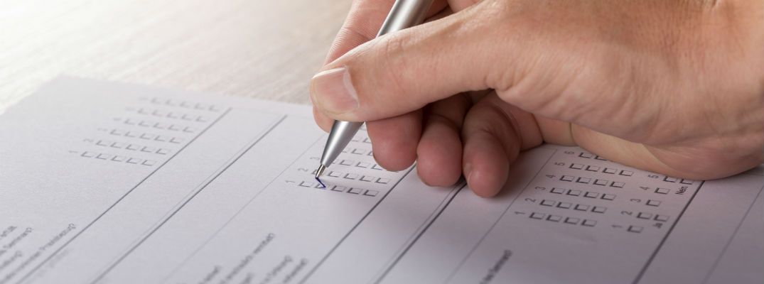 A stock photo of a person filling out a survey.