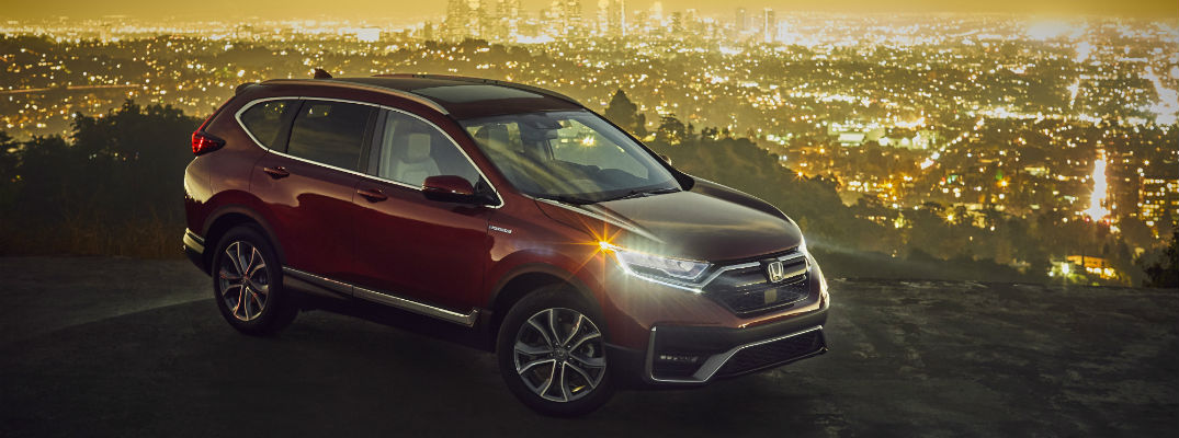A right profile photo of the 2020 Honda CR-V Hybrid parked over a city.