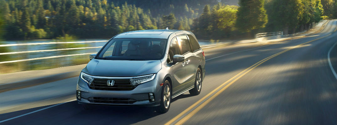 A front-end photo of the 2021 Honda Odyssey in motion on the road.
