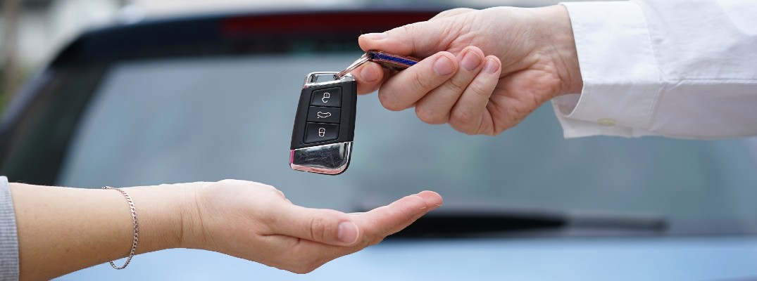 A stock photo of a person handing a set of keys to another person.