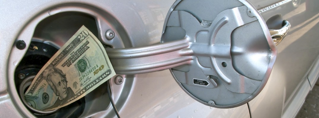 A stock photo illustration of a 20-dollar bill sticking out of a gas tank.