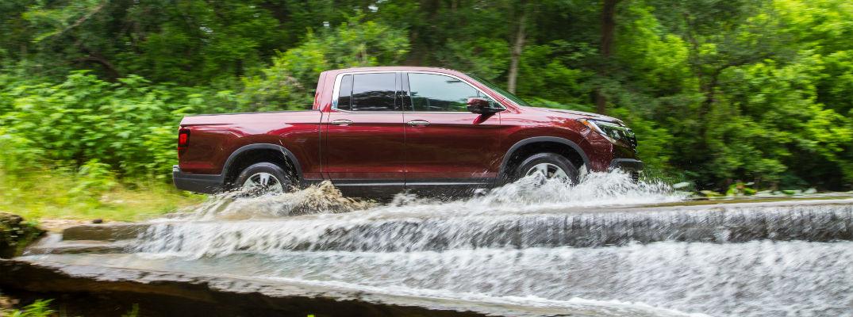 A right profile photo of a 2020 Honda Ridgeline crossing a stream.