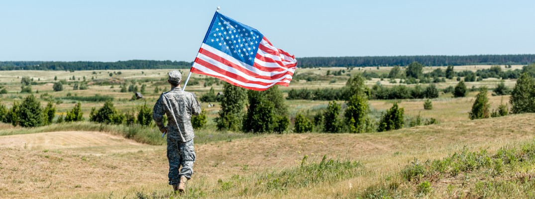 A stock photo of a soldier holding an American flag in a field.