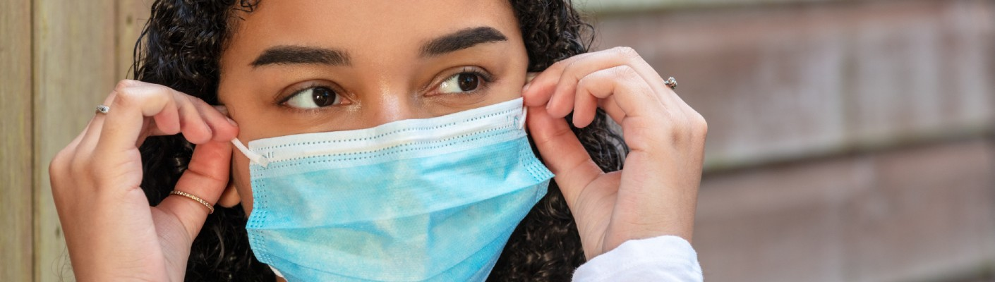 A stock photo of a person wearing a surgical facemask.