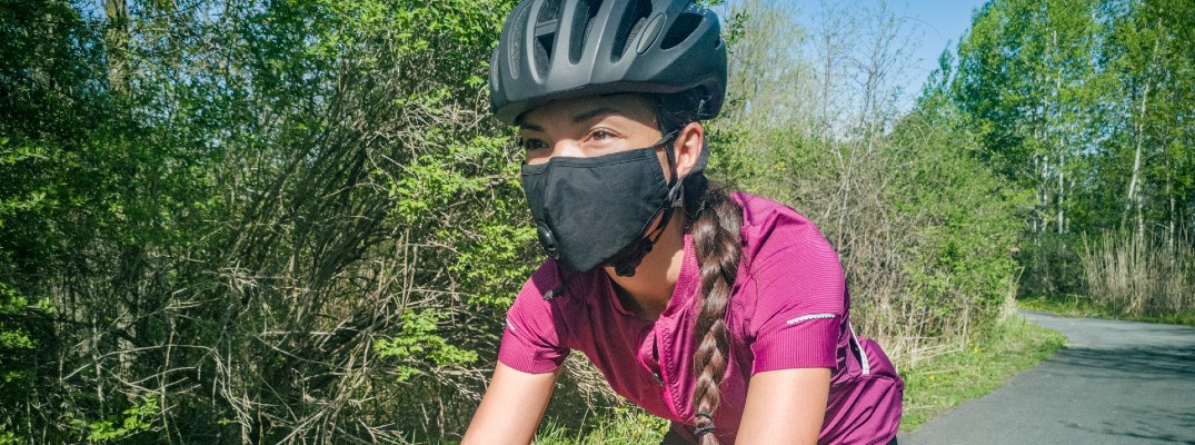 A stock photo of a person wearing a mask and riding a bike.