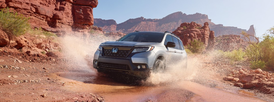 A photo of the 2021 Honda Passport driving through a deep puddle in the desert.
