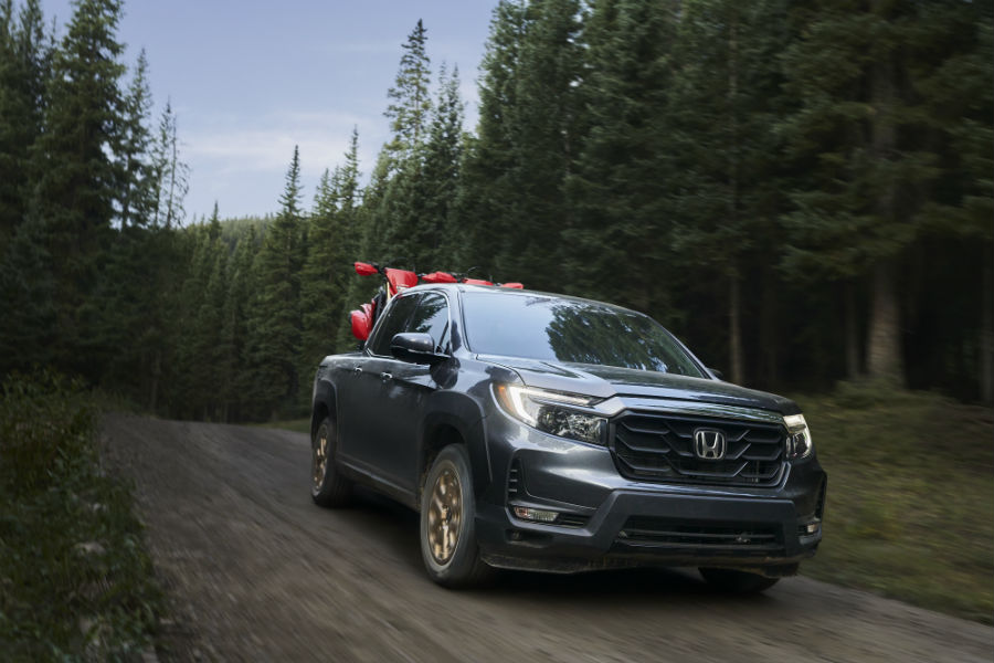 A front-end photo of the 2021 Honda Ridgeline hauling dirt bikes through the woods.