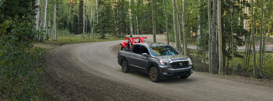 A photo of the 2021 Honda Ridgeline driving through the woods.