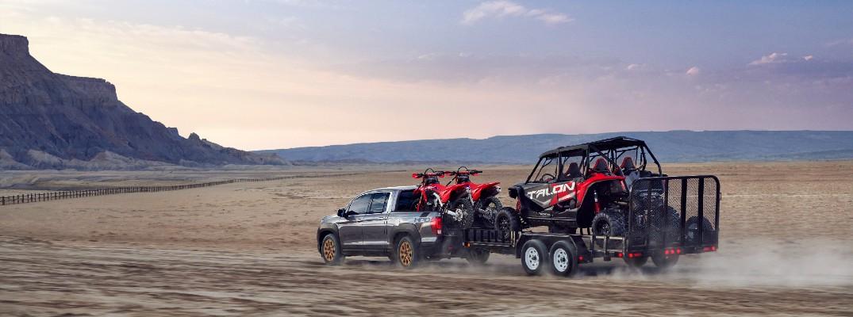 A photo of the 2022 Honda Ridgeline pulling a trailer.
