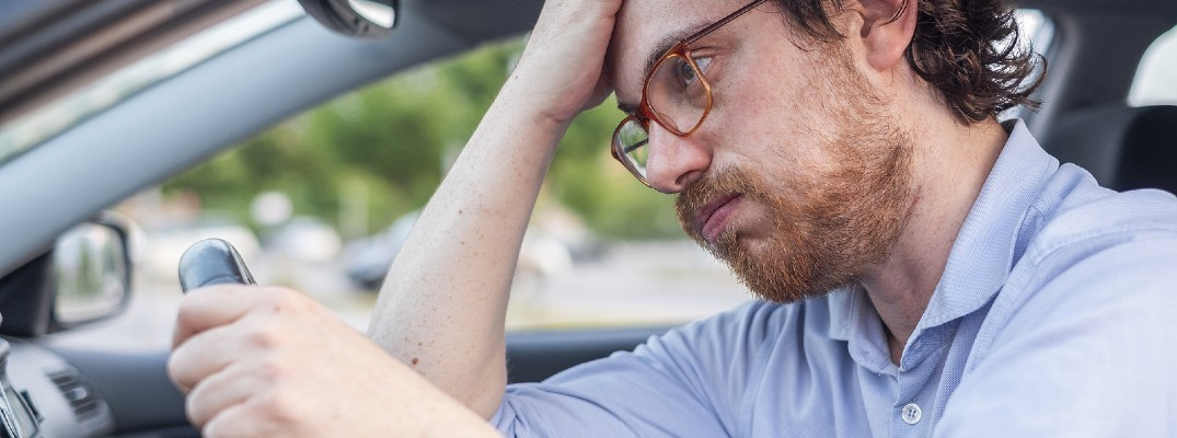 A stock photo of a frustrated person behind the wheel of their vehicle.