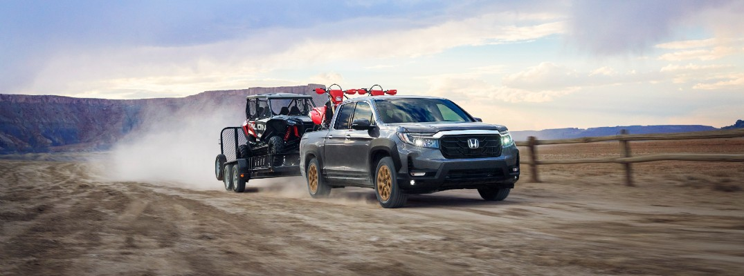 A photo of the 2021 Honda Ridgeline pulling a trailer on a gravel road.