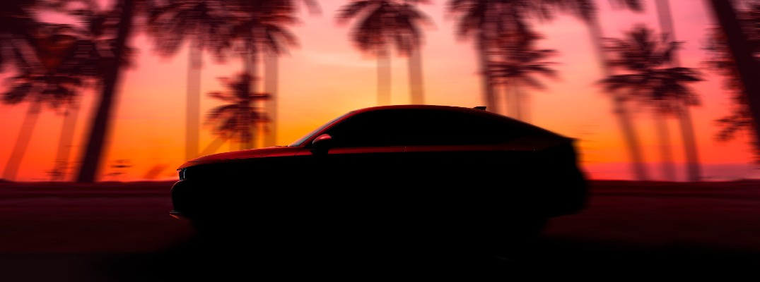 A silhouetted photo of the 2022 Honda Civic Hatchback on the road.