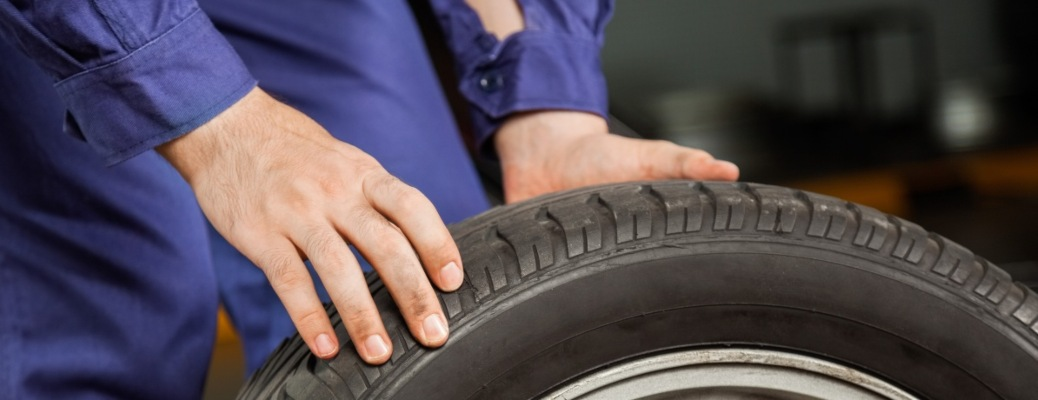 Man holding a tire and wheel
