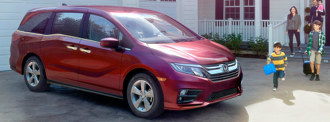 Red Honda Odyssey parked in front of building with people walking towards it