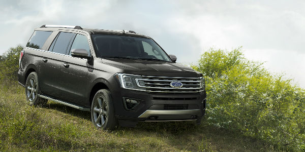 Black  Ford Expedition Descending Grassy Hill