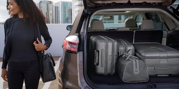 Woman Standing Next To  Ford Edge With Luggage In The Cargo Area