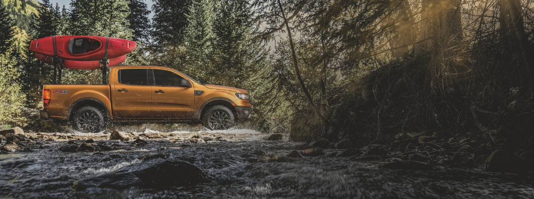 Orange 2019 Ford Ranger with Kayak on a Rack Fording a River