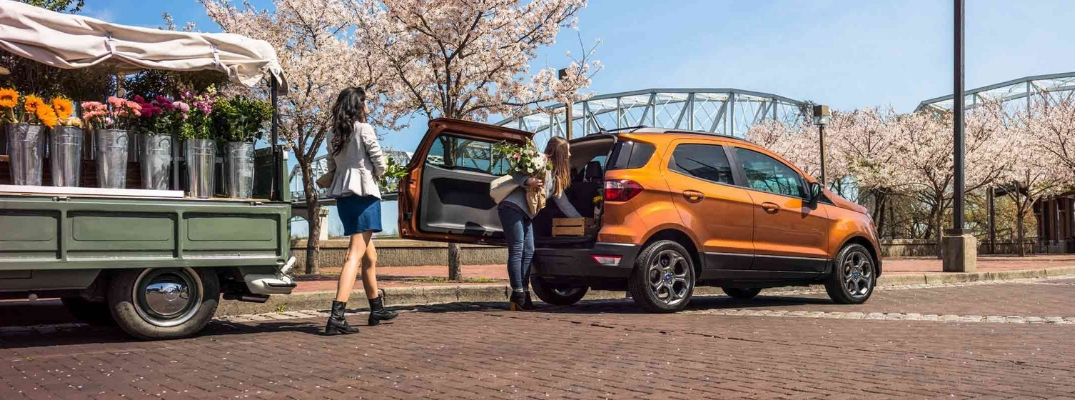 Two Women Loading Flowers into the Rear of an Orange 2019 Ford EcoSport