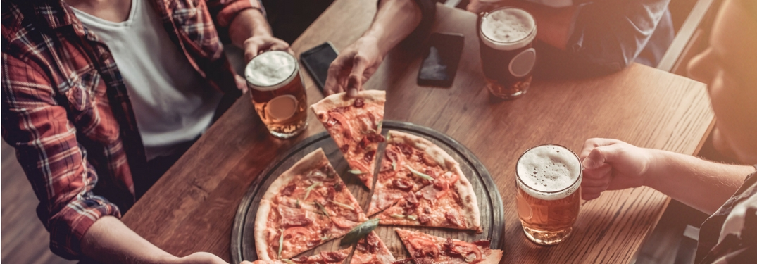 people eating pizza and drinking beer at a bar