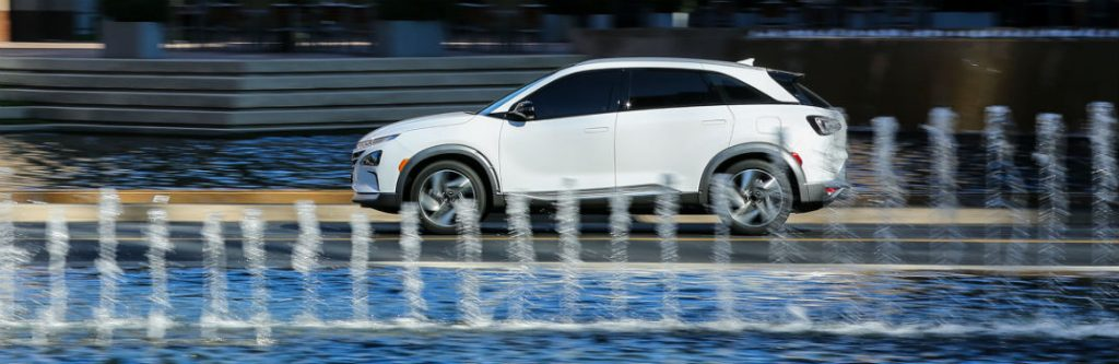 hyundai nexo driving by fountain side view
