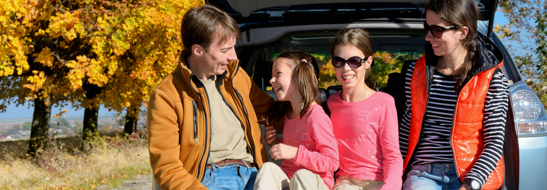 family-sitting-on-back-bumper-of-car-smiling-during-autumn