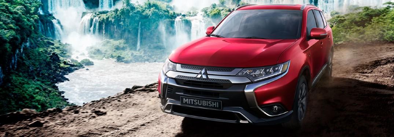 2020 Mitsubishi Outlander lado del conductor estacionado cerca de la cascada