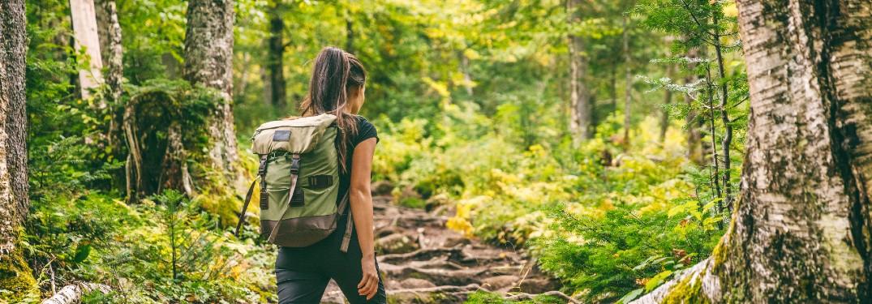 mujer de senderismo en el bosque con una mochila