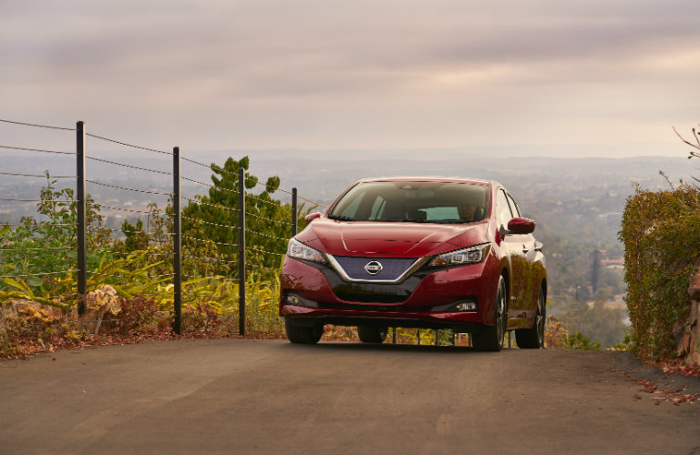 red nissan leaf driving on dirt road near fence