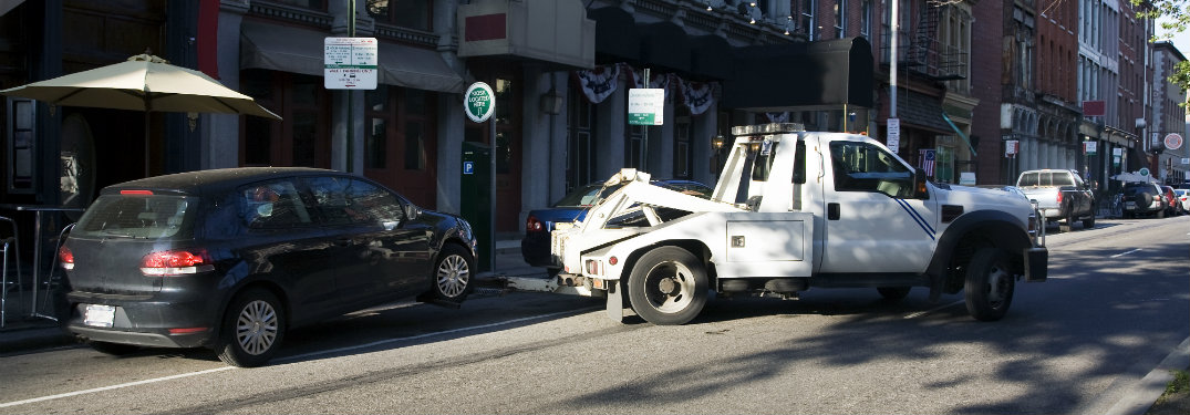 white tow truck pulling black hatchback