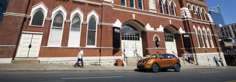 orange rogue sport in front of big brick building
