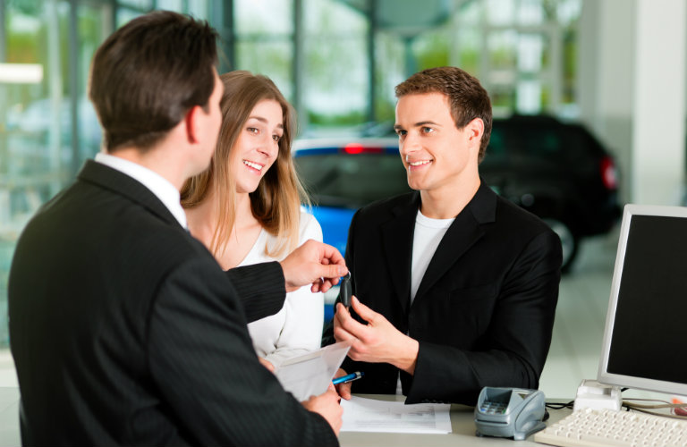 salesman handing keys to man at desk