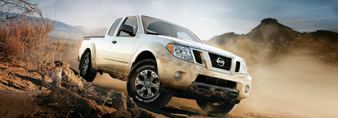 white nissan frontier driving on rocks and dirt