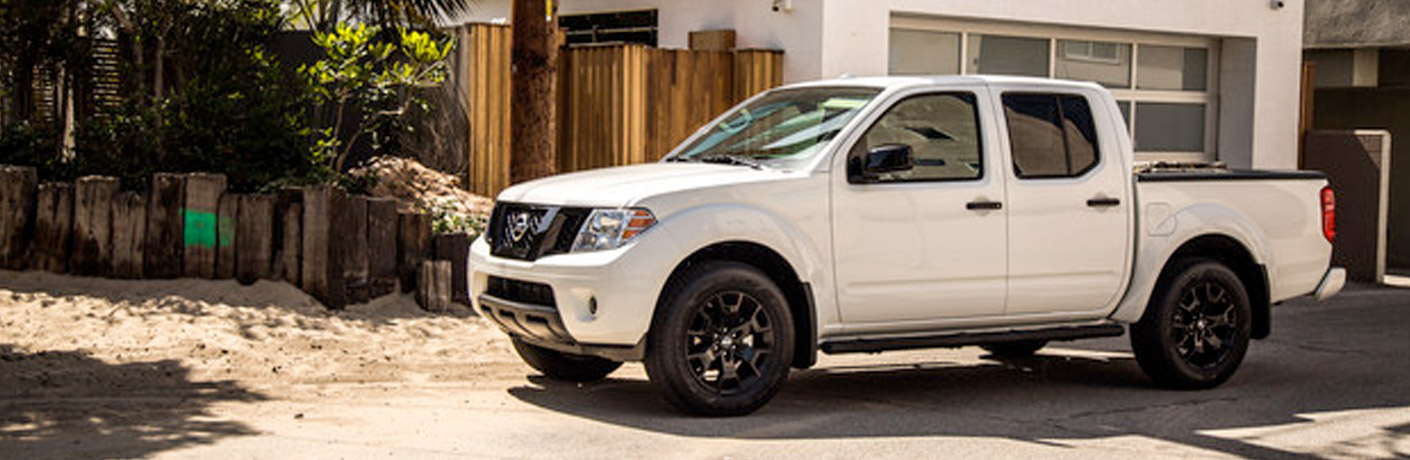 Exterior view of a white 2019 Nissan Frontier parked outside a home during the day