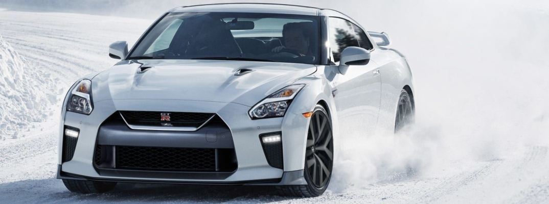 Exterior view of a white 2019 Nissan GT-R driving through the snow