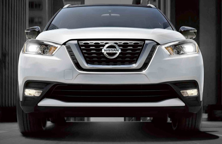 Exterior view of the front of a white 2019 Nissan Kicks parked in the city