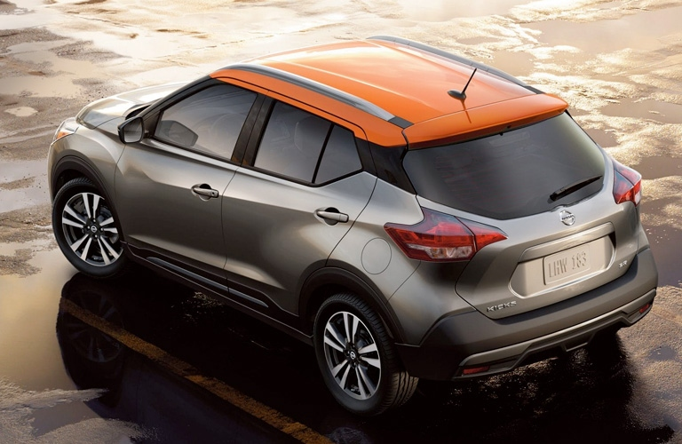Exterior view of a grey and orange 2019 Nissan Kicks parked in an empty parking lot