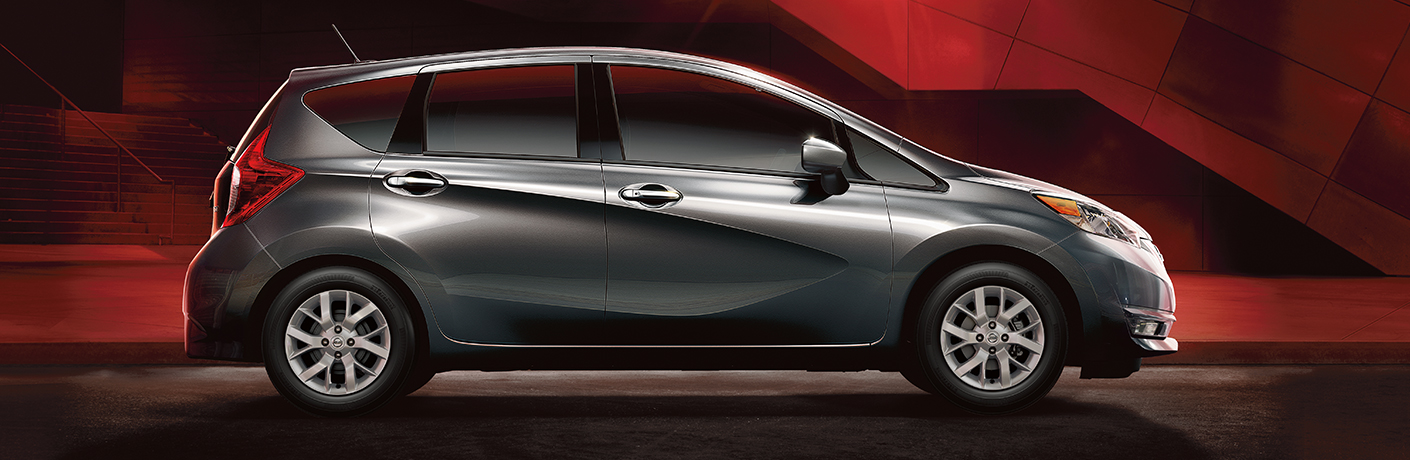 Exterior view of a gray 2019 Nissan Versa Note parked in a red and black showroom